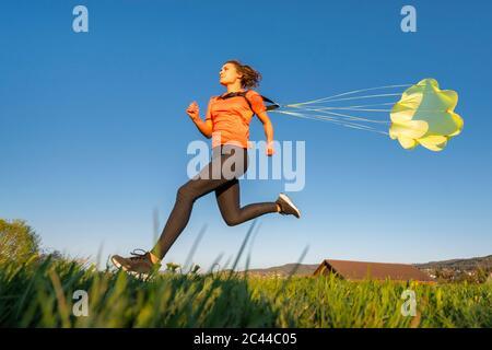 Vista ad angolo basso della giovane donna che si springe con paracadute contro il cielo azzurro