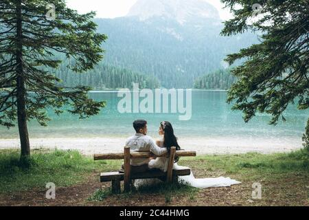 Una giovane coppia - lo sposo e la sposa sono seduti su una panchina sullo sfondo del lago e si guardano l'un l'altro. Foto Stock
