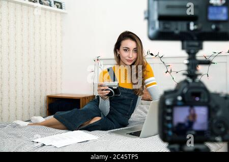 Giovane donna con lunghi capelli marroni seduto sul letto con macchina fotografica e portatile, registrazione blog. Foto Stock