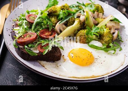 Colazione con uova fritte, broccoli, funghi e panino di pomodoro. Cibo sano ed equilibrato.
