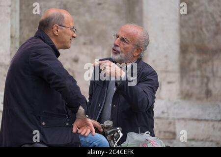 Due italiani parlano con l'altro sulla piazza del Popolo di Ascoli Piceno, Italia. L'uomo destro usa un gesto con la mano