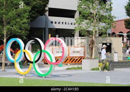 Un monumento agli anelli Olimpici situato fuori dal Museo Olimpico del Giappone. Una statua del fondatore delle Olimpiadi Pierre de Coubert e lavori stradali sono sullo sfondo.