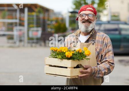 Vita in su ritratto di giardiniere anziano allegro che tiene i fiori e guardando la macchina fotografica mentre si sta in piedi dal mercato dell'albero all'aperto, spazio di copia Foto Stock