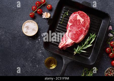 Vista dall'alto Black Angus prime Beef costolette di manzo con bistecca alla griglia in ghisa, rosmarino fresco, pomodori ciliegini, olio d'oliva e spezie. Layout creativo con