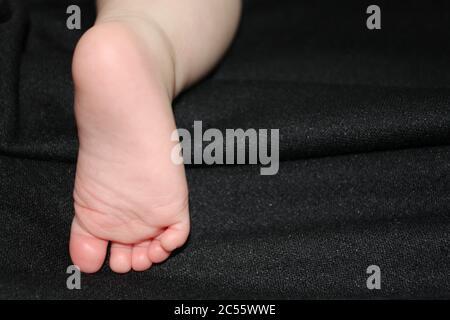 Piede neonato della bambina grande su sfondo nero. Foto Stock