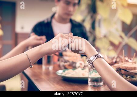La famiglia prega prima della cena del Ringraziamento a casa.