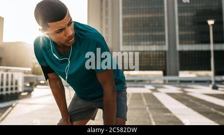 Atleta maschile che si appoggia in avanti con le mani sulle ginocchia e guarda lontano in città. Uomo corridore che fa una pausa dopo la corsa di mattina.