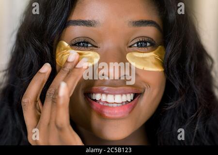 Anti invecchiamento, cura della pelle, concetto di cosmetologia. Primo piano ritratto di bellezza di affascinante giovane donna africana sorridente applicando macchie d'occhio medico dorate Foto Stock
