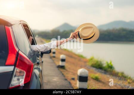Donna in un momento di relax e di piacere viaggio. Giovane asiatico appella femmina dentro auto nera compatta con sollevare il cappello fuori alla finestra auto wit