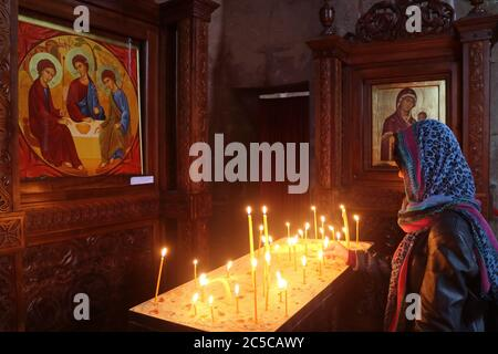 Donna che offre una candela nella storica Chiesa del Monastero di Jvari, Mtskheta, l'ex capitale della Georgia