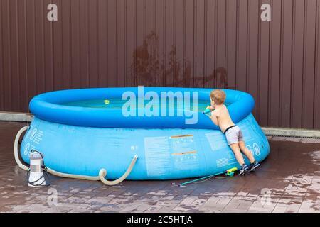 Carino piccolo adorabile ragazzo biondo caucasico che guarda in piscina blu gonfiabile Godetevi giocando con canna da pesca giocattolo nel cortile di casa il caldo giorno estivo Foto Stock