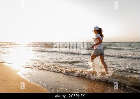 Una giovane donna che corre vicino al mare. Sport Foto Stock