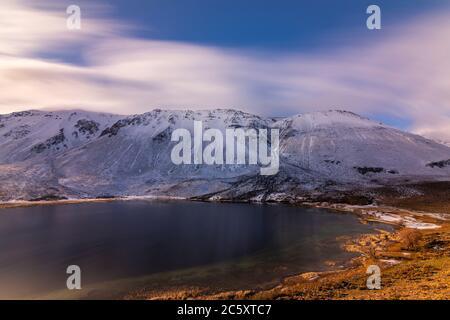 Lunga esposizione di un lago di montagna contro le montagne innevate durante il tramonto in inverno, Esquel, Patagonia, Argentina Foto Stock