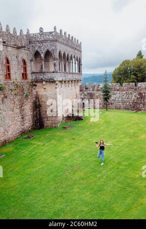 Giovane turista femminile che corre sull'erba sul Castello di Soutomaior in Galizia, Spagna