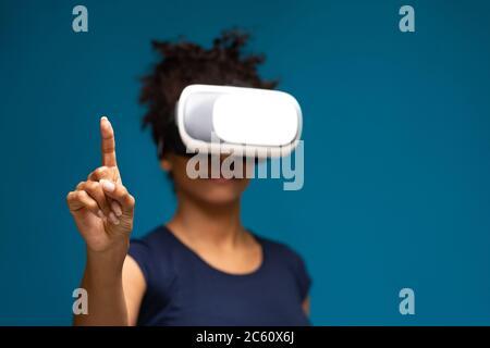 Donna afro-americana che usa il visore VR, toccando il touchscreen invisibile Foto Stock