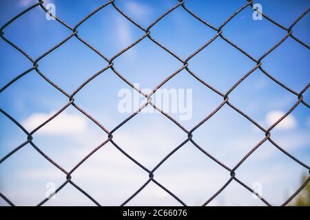 Cielo blu con nuvole attraverso la recinzione arrugginita della rete metallica. Bordo di protezione e linea non consentita. Sfocatura dello sfondo, texture. Primo piano della gabbia di collegamento, wallpa