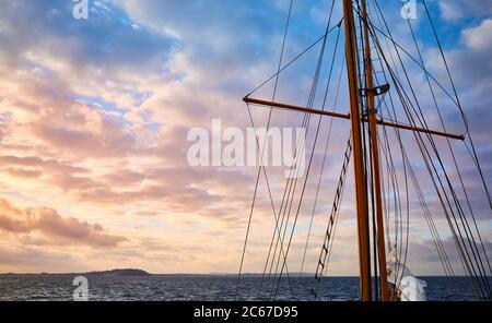 Vecchio albero della nave a vela a bella alba, concetto di viaggio. Foto Stock