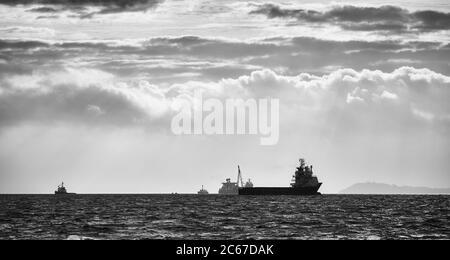 Immagine in bianco e nero delle silhouette delle navi all'orizzonte al tramonto.