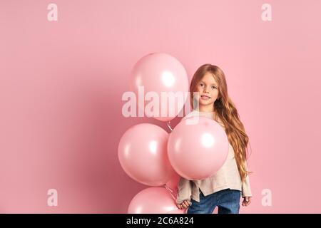 Bella bambina che indossa blusa bianca stand tenendo palloncini d'aria rosa, posa guardare la macchina fotografica e sorriso. Isolato su sfondo rosa Foto Stock