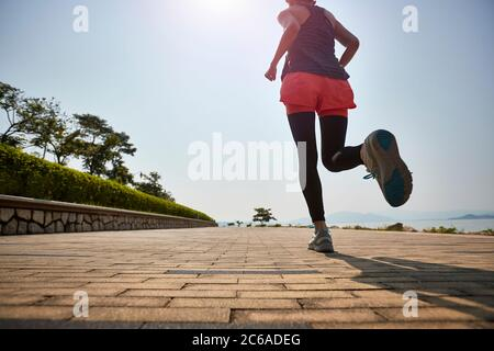giovane donna asiatica adulta che corre jogging all'aperto, vista posteriore e angolo basso