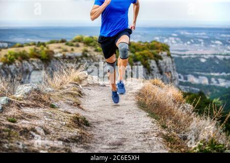 corridore maschio in ginocchiere che corrono su stretto sentiero di montagna Foto Stock