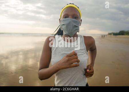Nuovo allenamento normale di corsa sulla spiaggia di donna afroamericana - giovane attraente e atletica ragazza nera in maschera di faccia formazione all'aperto facendo post quaran