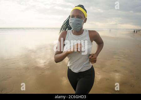 Nuovo normale allenamento di corsa sulla spiaggia di donna afro americana - giovane attraente e atletica ragazza nera in maschera di formazione all'aperto facendo post quarantin