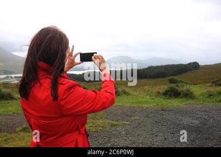 Donna in rosso cappotto turistico scattare una fotografia a Loch Tulla, negli higllands della Scozia sulla strada per Glencoe agosto 2019 attraente signora