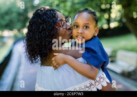 Primo piano ritratto di piccola cute sorridente ragazza africana bambino in abito blu, guardando la macchina fotografica, mentre abbracciando bella madre, baciandola nella guancia