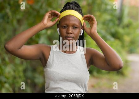 Running girl lifestyle ritratto - giovane attraente e fit donna afro americana nera regolazione fascia per capelli prima di outdoor allenamento in campagna Foto Stock