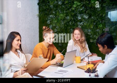 Lavoro di squadra di successo di giovani e diverse persone d'affari, partner commerciali donne che collaborano insieme utilizzando un computer portatile. Moderno ufficio bianco con parete verde Foto Stock