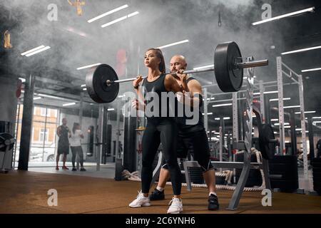 Giovane donna sportiva si è concentrata sul sollevamento pesante barbell, facendo squat con calma forte viso, esprimendo fiducia in palestra, allenandosi insieme con capelli senza