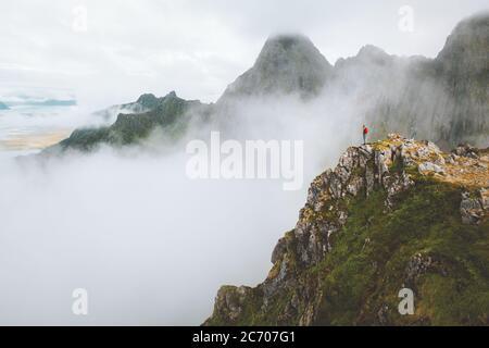 Uomo in piedi da solo sul bordo della scogliera di montagna nebbia natura viaggio attivo sano stile di vita all'aperto avventura vacanze in Norvegia Foto Stock
