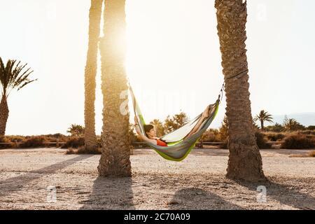 Donna che giace in amaca tra palme sulla spiaggia
