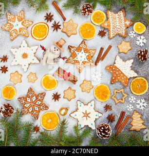 Biscotti allo zenzero natalizio in forma di fiocchi di neve, arancio secco, anice stellato e pupazzo di neve su fondo di pietra grigia. Vista dall'alto. Simboli di Capodanno e Chr