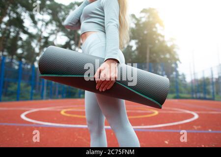 Concetto di fitness, sport e stile di vita sano. Immagine tagliata di giovane ragazza in grigio sport indossare, tenendo tappetino per l'esercizio e camminare all'aperto allo sport Foto Stock