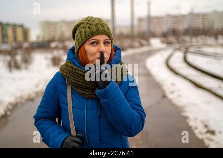 Bella giovane donna dai capelli rossi in abiti casual sorride e fa gesto di silenzio con indice dito sulle labbra. Il concetto di silenzio.
