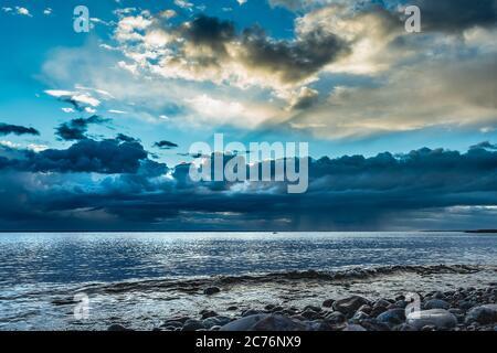 Il mare dopo una tempesta sul Mar Baltico svedese al tramonto dove i raggi del sole si illuminano tra le nuvole e il cielo comincia a ridirarsi blu Foto Stock