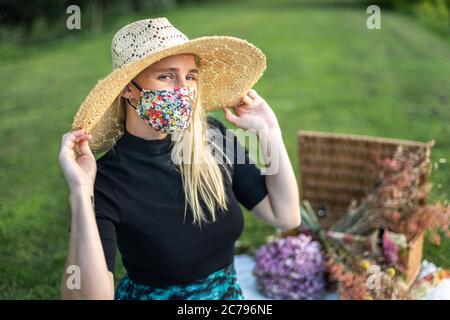 Bella giovane donna che indossa una maschera elegante e alla moda del coronavirus durante il blocco pandemico Covid-19 Foto Stock