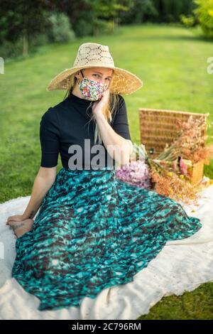Donna che indossa una maschera di coronavirus che copre durante la pandemia di Covid-19 in un tiretto editoriale di moda Foto Stock