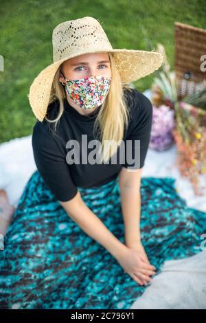 Ritratto di una donna con capelli biondi che indossa una maschera di coronavirus durante il blocco pandemico Covid-19 Foto Stock