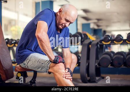 Un ritratto di calvo uomo anziano che sente forte dolore al ginocchio durante l'allenamento in palestra. Concetto di persone, assistenza sanitaria e stile di vita