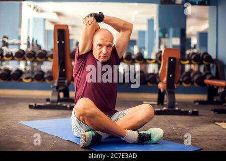 Un ritratto di calvo uomo anziano che fa stretching dopo l'allenamento in palestra. Concetto di persone, assistenza sanitaria e stile di vita Foto Stock