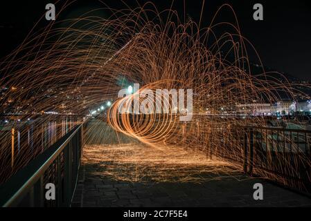 Colpo orizzontale di lana d'acciaio su un ponte con ringhiere metalliche di notte a Como, Italia