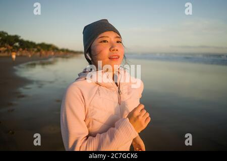 Ragazza asiatica che corre sulla spiaggia - giovane attraente e felice coreana che fa jogging esercizio in bella spiaggia godendo di fitness e corridore sano Foto Stock