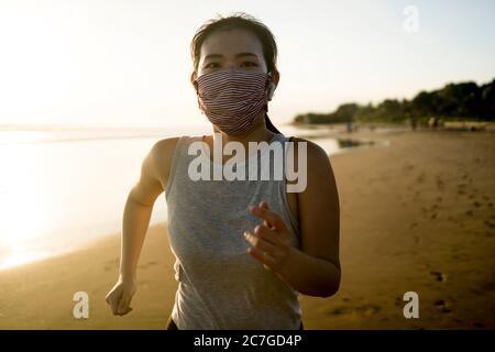 Nuovo normale allenamento di corsa di ragazza asiatica in maschera di faccia - giovane felice e attraente donna cinese che fa jogging sulla spiaggia in quarantena post esterno exer