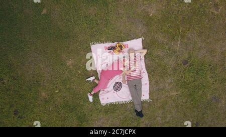 Weekend di famiglia picnic nel parco. La gente anziana, coppia caucasica anziana attiva si trovano sulla coperta su prato verde erba. Vista aerea. Scatta dal drone. Uomo anziano, donna. Festeggiamenti per l'anniversario. Nonni