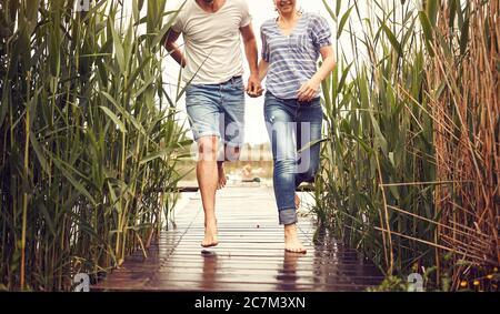 Coppia che corre nel rain.Happy uomo e donna sullo stagno il giorno piovoso insieme.