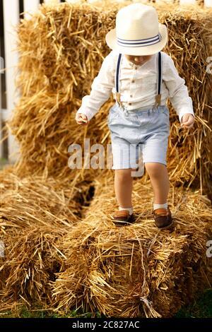 Un ragazzo in un cappello di paglia e pantaloncini eleganti con sospenditori su un pagliaio.