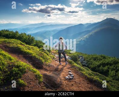 Montagne e giovane donna in piedi con zaino sul sentiero